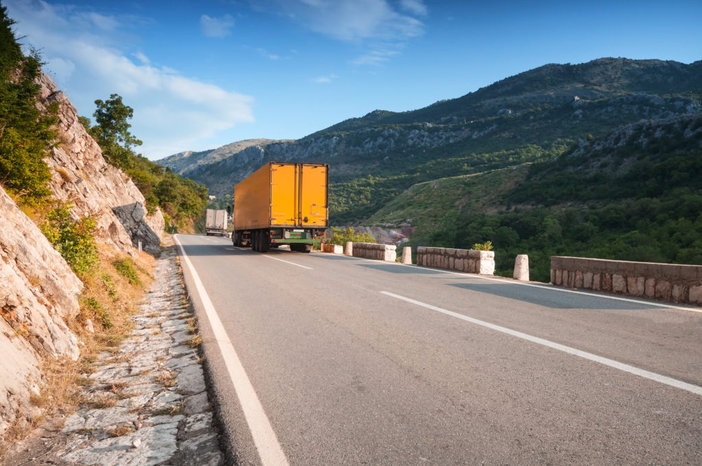 Trucks driving on asphalt mountain road in Montenegro